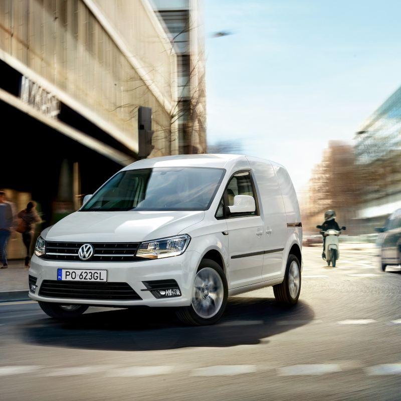Volkswagen Caddy Furgon dynamicznie przejeżdża przez miasto.