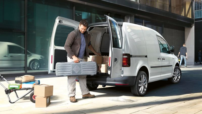 The rear of the VW Caddy Panel Van with its rear wing doors open viewed at an angle. A tradesman is unloading tools and materials from the spacious load compartment.