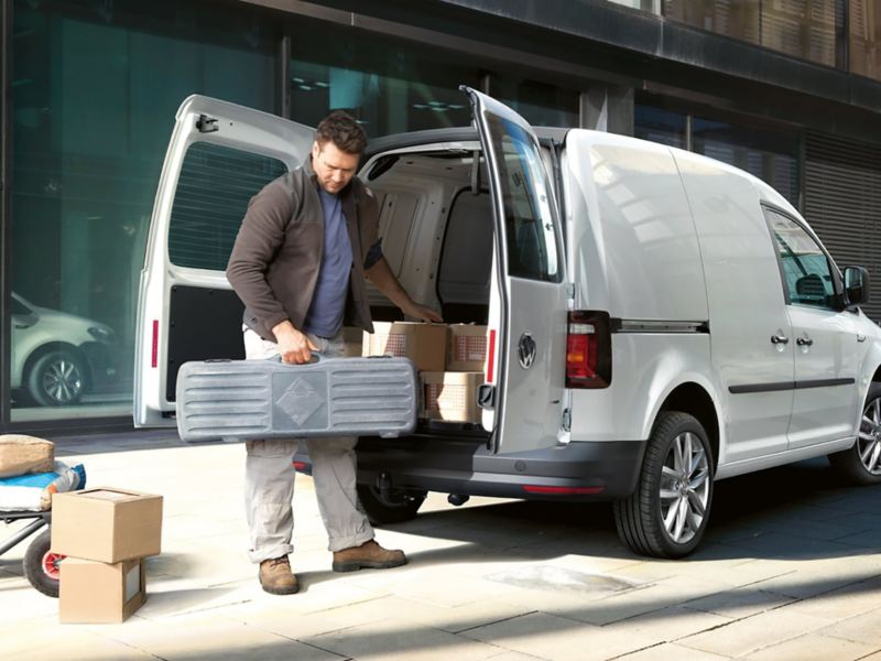 The rear of the Caddy Delivery Van with its rear wing doors open viewed at an angle. A tradesman is unloading tools and materials from the spacious load compartment.