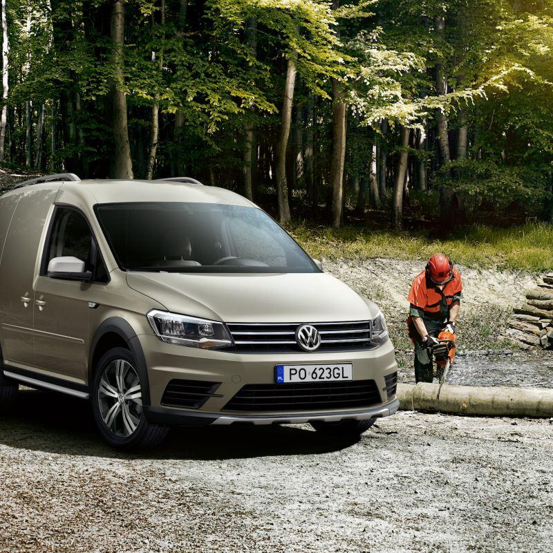 Samochód dostawczy Volkswagen Caddy Furgon Alltrack w lesie z robotnikami leśnymi.