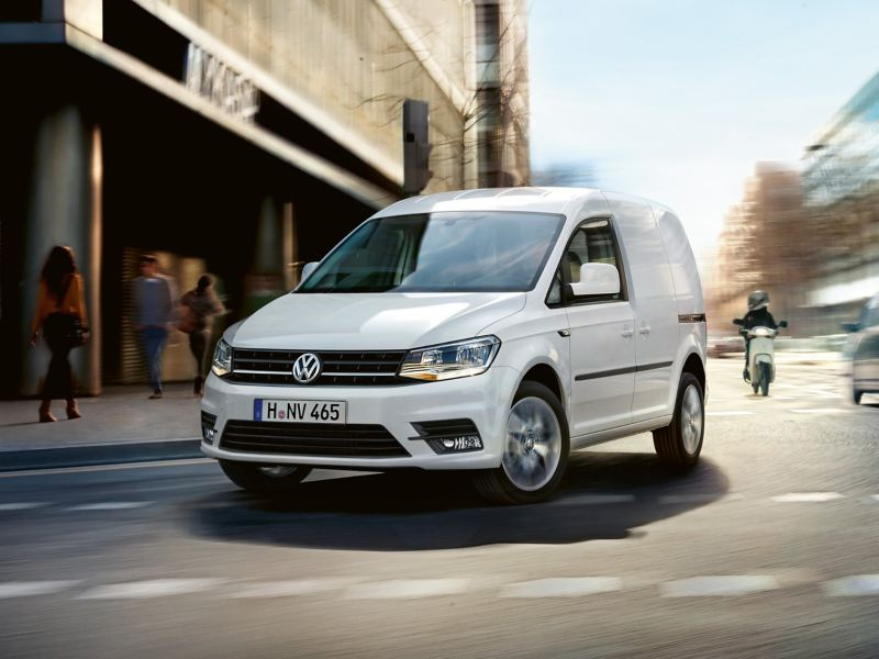 A white Volkswagen Caddy Panel Van drives dynamically through a busy city.