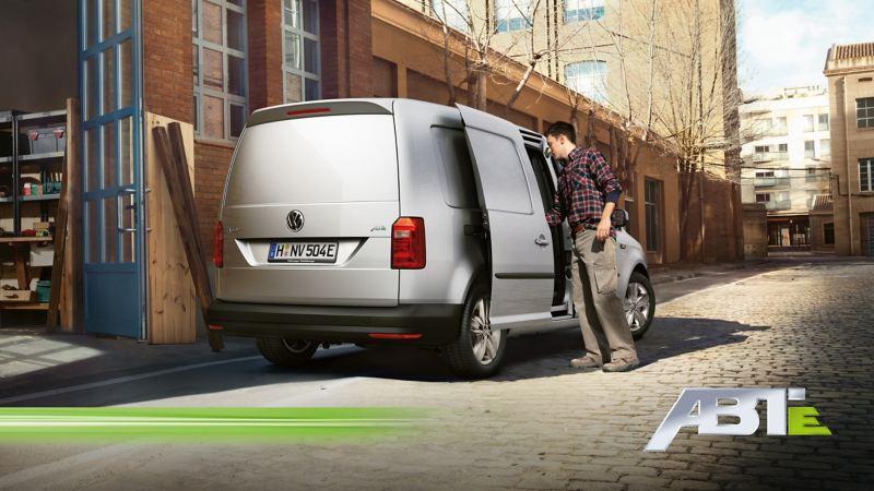 Ein Mann steht neben einem ABT e-Caddy und greift durch die Seitentür in den Innenraum.
