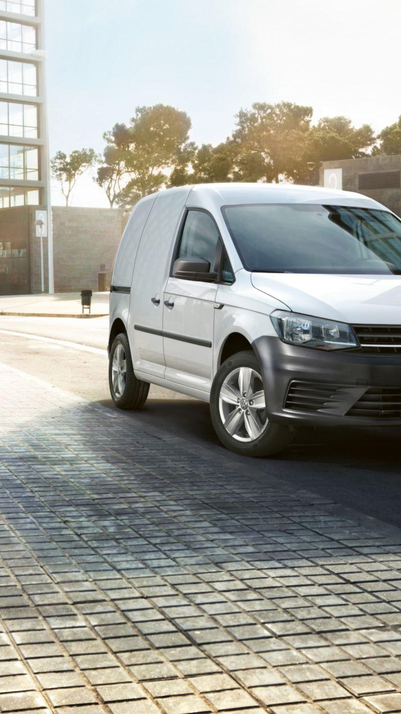 Biały Volkswagen Caddy Furgon zaparkowany na poboczu drogi. W tle widać nowoczesne biurowce.