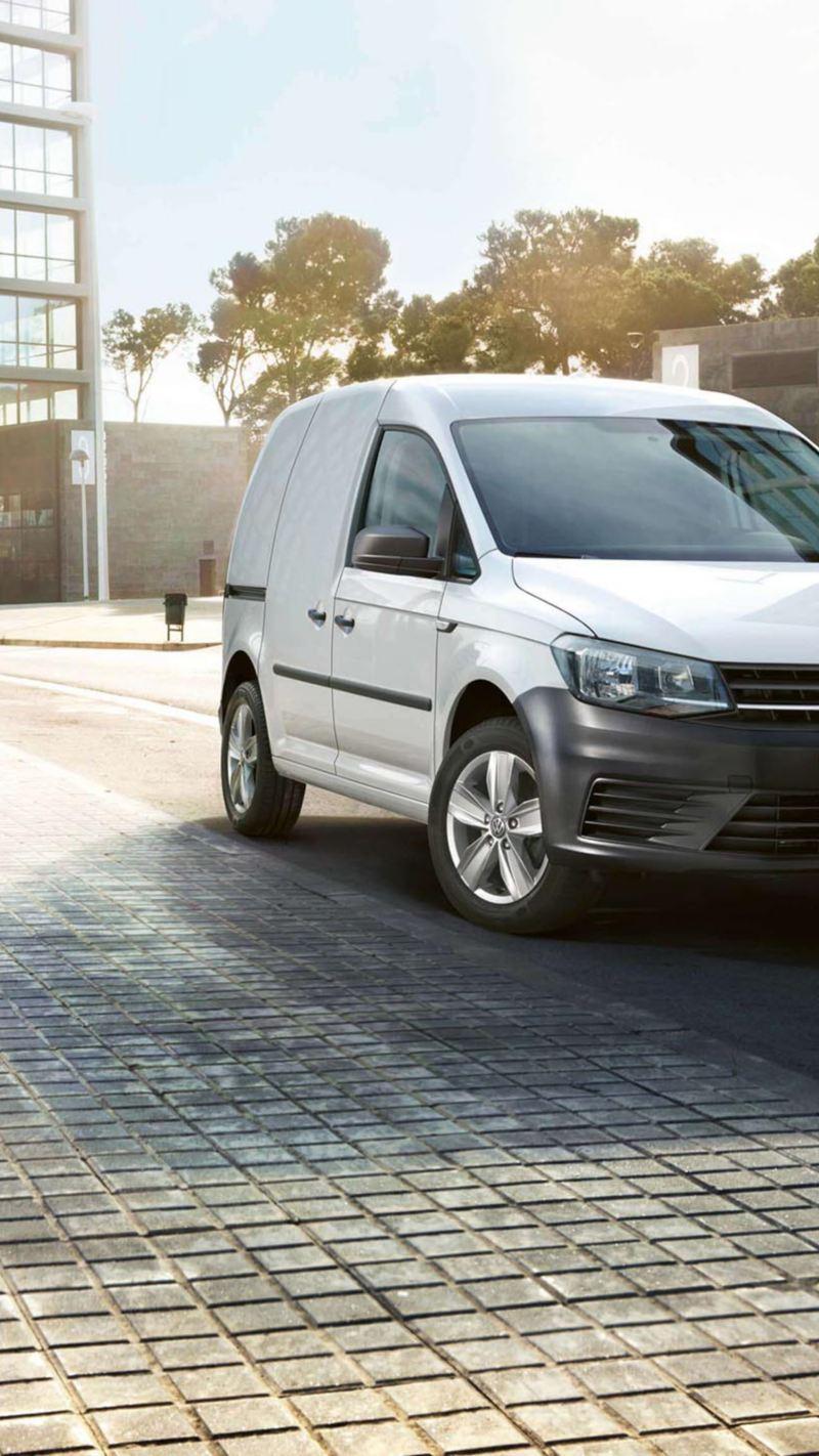 Ένα Volkswagen Caddy Van, σταματημένο στην άκρη του δρόμου. Πίσω, υψώνονται μοντέρνα κτήρια γραφείων.