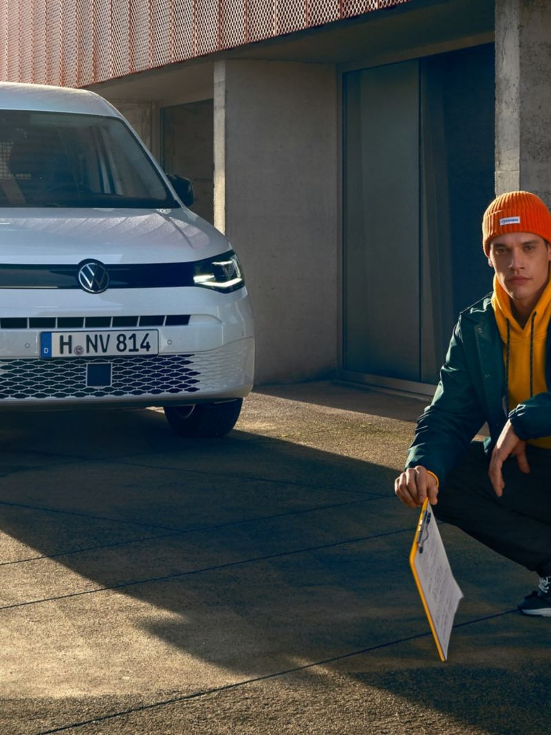The new Volkswagen Caddy Cargo in front of a modern building complex.