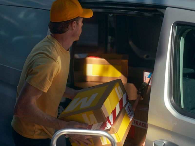 A man loading the new Volkswagen Caddy Cargo with packages.