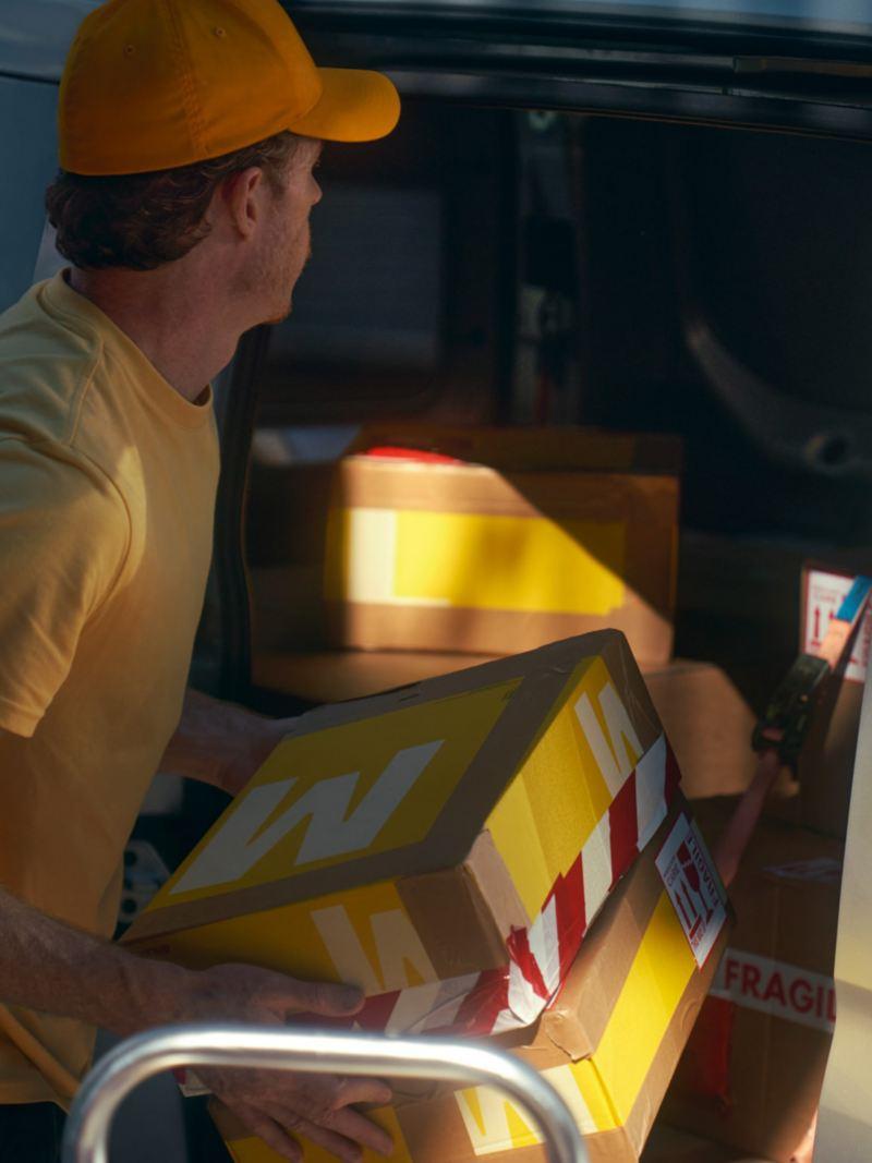Ein Mann belädt den neuen Volkswagen Caddy Cargo mit Paketen.