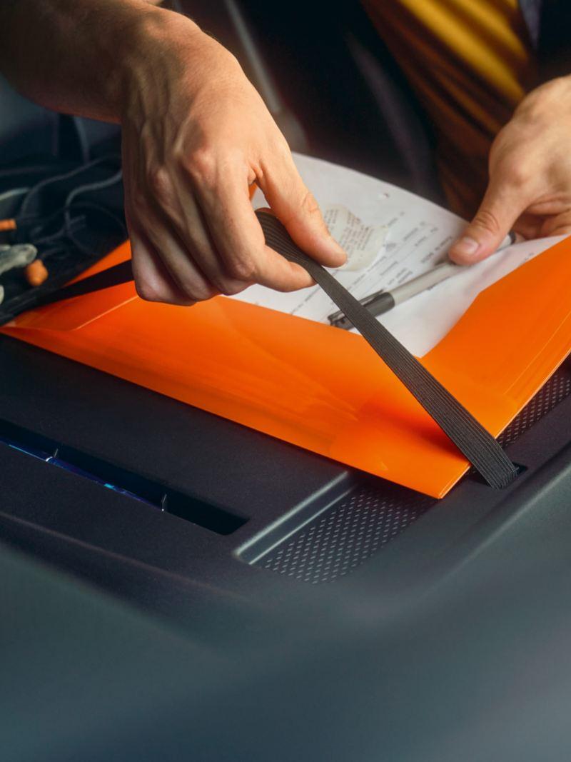 Ein Mann fixiert eine Mappe am Rücken des Beifahrersitzes vom neuen Volkswagen Caddy Cargo.