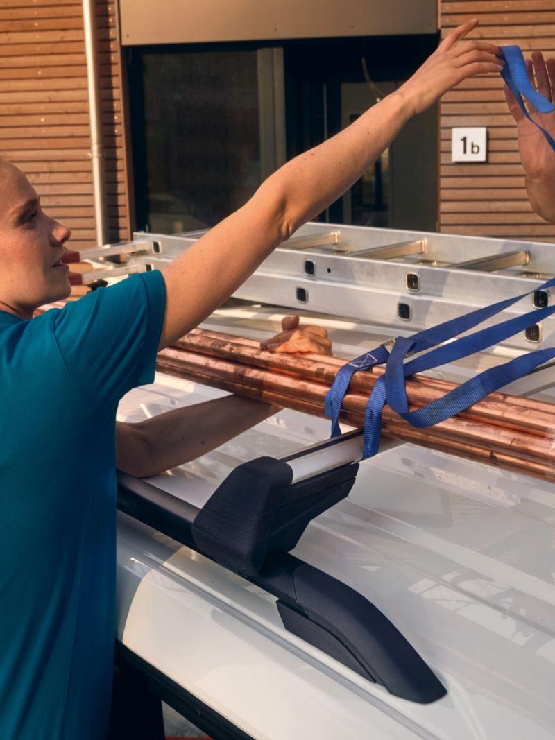 Eine Frau und ein Mann sichern eine Leiter auf dem Dach des neuen Volkswagen Caddy Cargo.