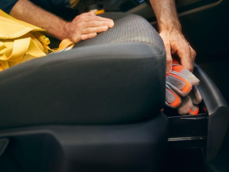 Ein Mann holt Handschuhe aus der Schublade am Unterboden der Beifahrersitzes des neuen Volkswagen Caddy Cargo.