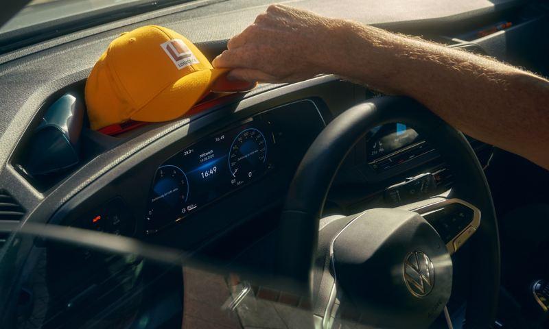 Ein Mann legt seine Cappie auf das Cockpit des neuen Volkswagen Caddy Cargo.