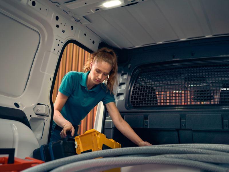 Eine Frau verstaut ihr Werkzeug im neuen VW Caddy Cargo.