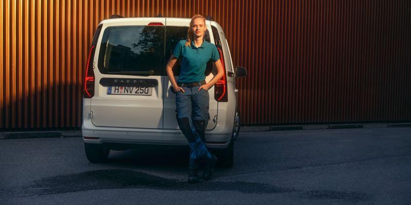 Eine Frau lehnt an die Heckflügeltüren des neuen Volkswagen Caddy Cargo.