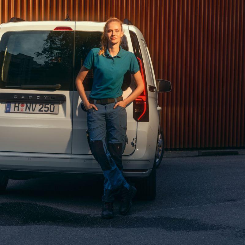 Kvinna framför en VW Caddy Cargo skåpbil