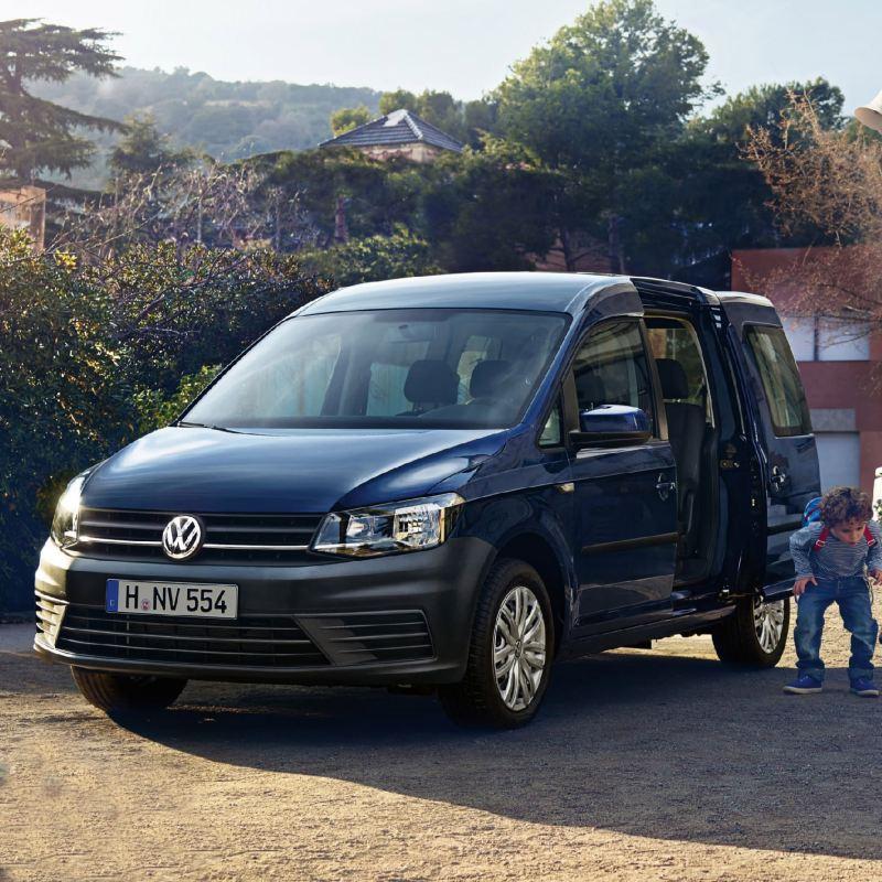 Blå Volkswagen vw caddy maxi foran skole familiebil 7 seter hund barn familie barnehage skolesekk skolebarn
