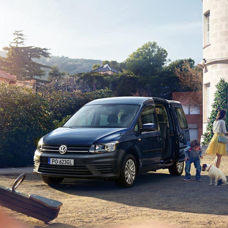 Niebieski Volkswagen Samochody Użytkowe Caddy przed szkołą. Matka odbiera syna po szkole.