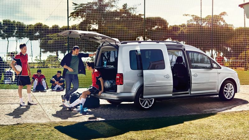 A silver VW Caddy with an open sliding door and open tailgate in front of a football pitch. A football player sits on the edge of the bumper.