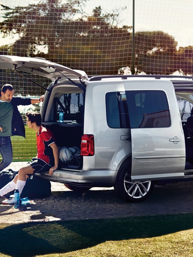 A silver Caddy with an open sliding door and open tailgate in front of a football pitch. A football player sits on the edge of the bumper.