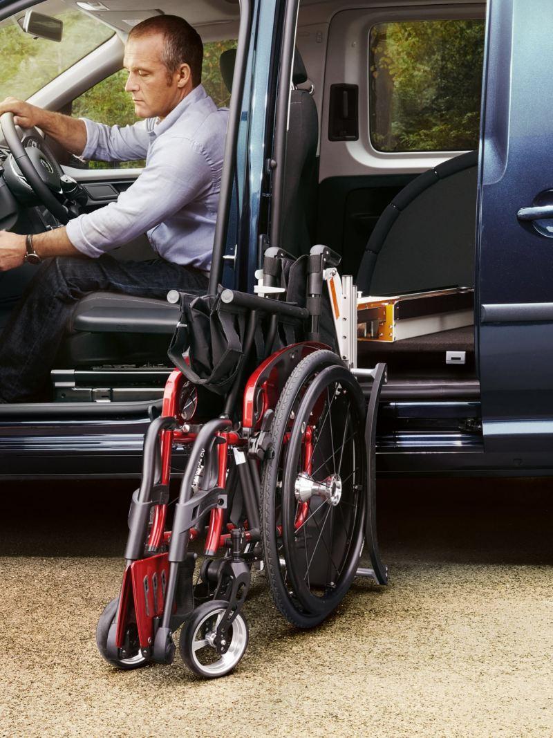 Ein Mann sitzt auf dem Fahrersitz eines Fahrzeugs und betätigt eine Taste für die Rollstuhlverladehilfe.