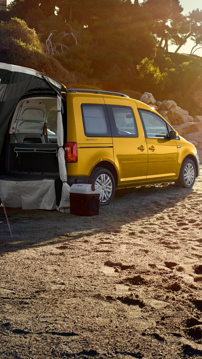 Le Caddy Beach camper est garé sur une plage, la tente disponible en option est déployée sur le hayon.