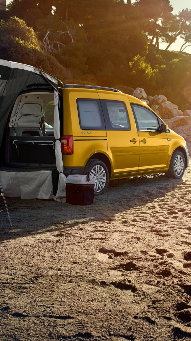 Caddy Beach zaparkowany na plaży, przy tylnej klapie rozstawiony jest opcjonalnie dostępny namiot.