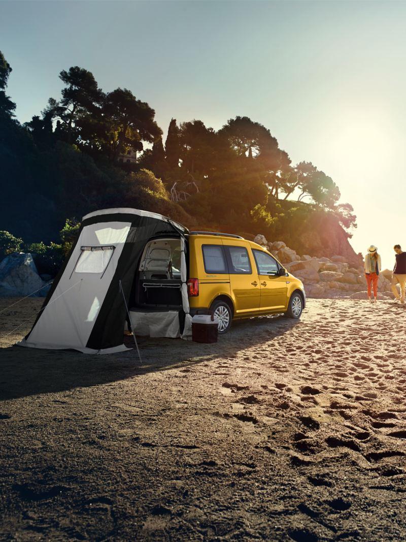 Caddy Beach parkuje na plaży, przy tylnej klapie rozstawiony jest opcjonalnie dostępny namiot.