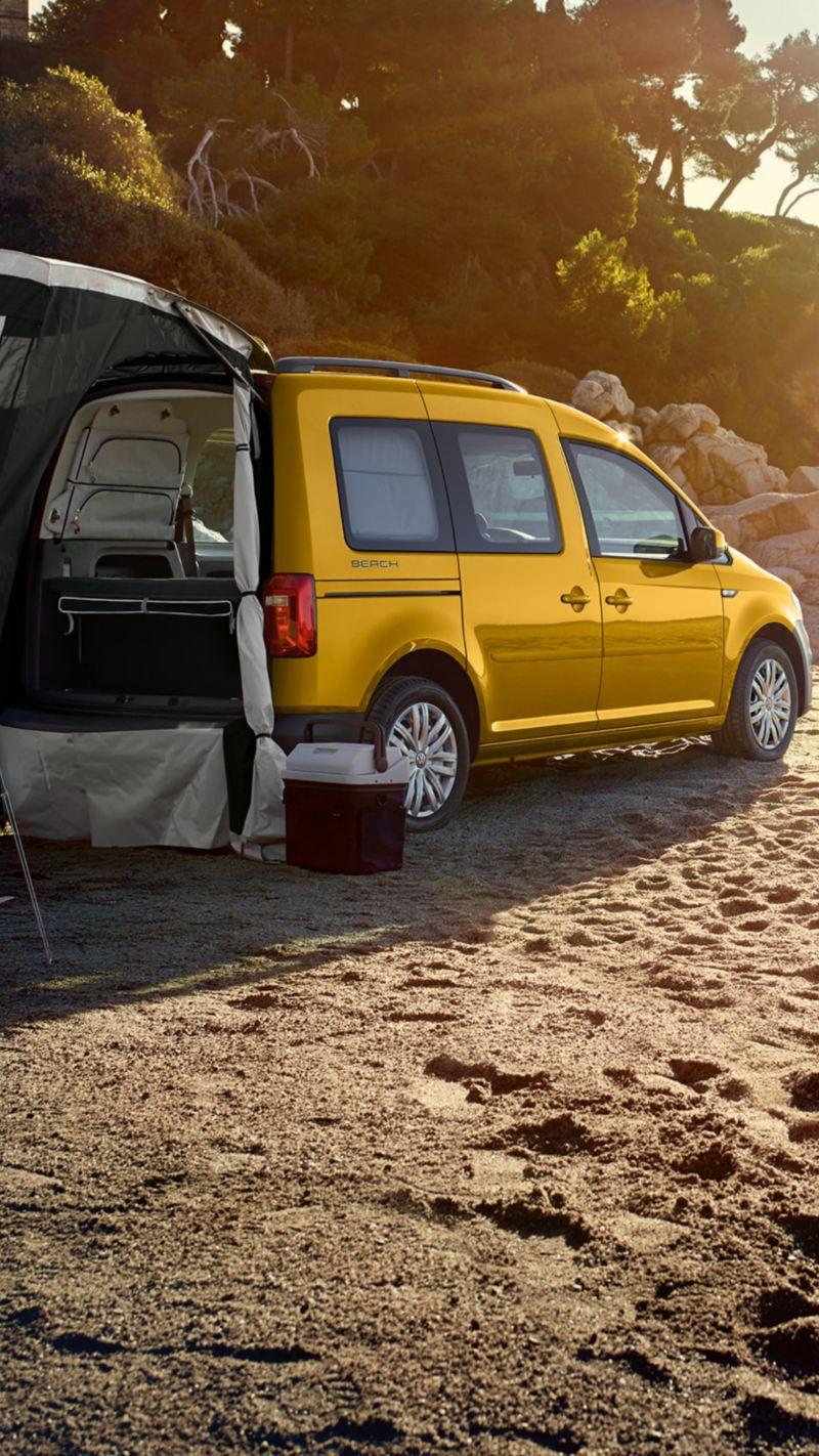 Der Caddy Beach parkt auf einem Strand, an der Heckklappe ist das optional verfügbare Zelt aufgeschlagen.