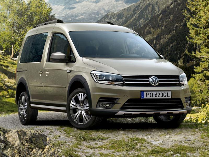Volkswagen Caddy Alltrack zaparkowany na skraju szutrowej drogi. Za nim zalesiony górski krajobraz.