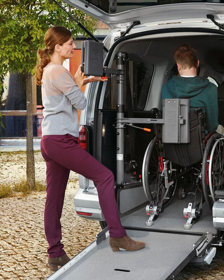 Eine Frau sichert einen Rollstuhlfahrer, der im Heck eines Caddy steht.