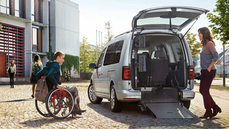 Ein junger Mann im Rollstuhl und eine Frau stehen an der geöffneten Heckklappe eines Caddy.