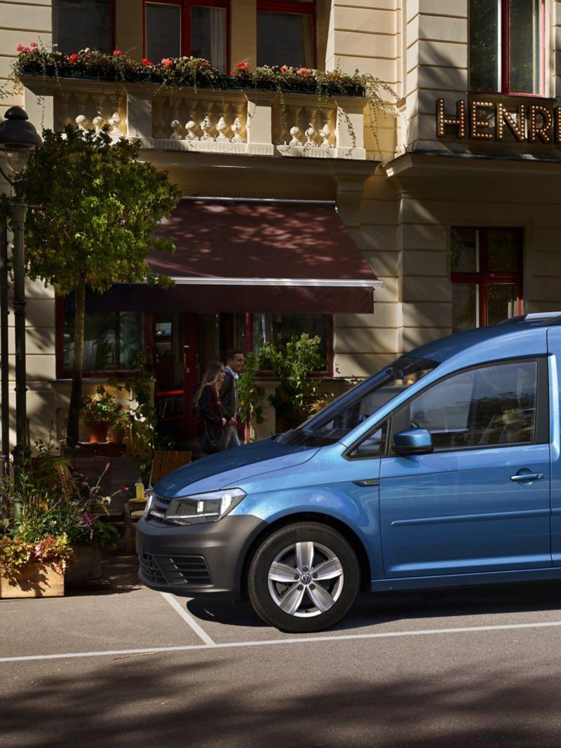 Volkswagen Caddy Xtra z boku. Zaparkowany przed hotelem w mieście.