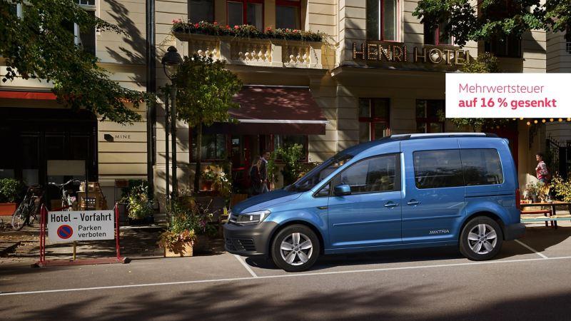 Der Caddy Xtra in Seitenansicht. Er steht vor einem Hotel in der Stadt.
