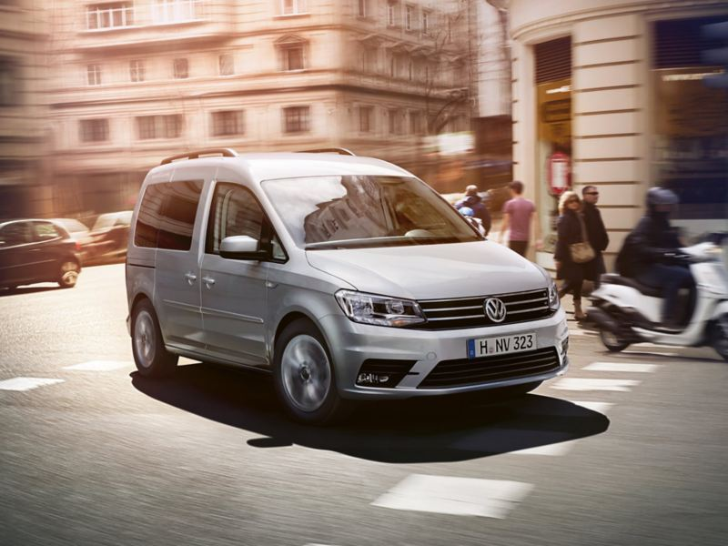 The Caddy Kombi drives dynamically through a busy city.