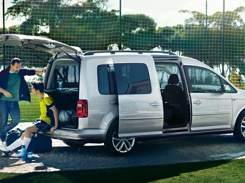 Silberfarbener Caddy mit geöffneter Schiebetür und geöffneter Heckklappe vor einem Fußballplatz. Ein Fußballspieler sitzt an der Stoßfängerkante.