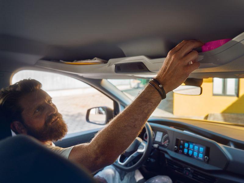 Ein Mann legt etwas im Ablagefach im Dachhimmel des neuen Caddy Kombi ab.