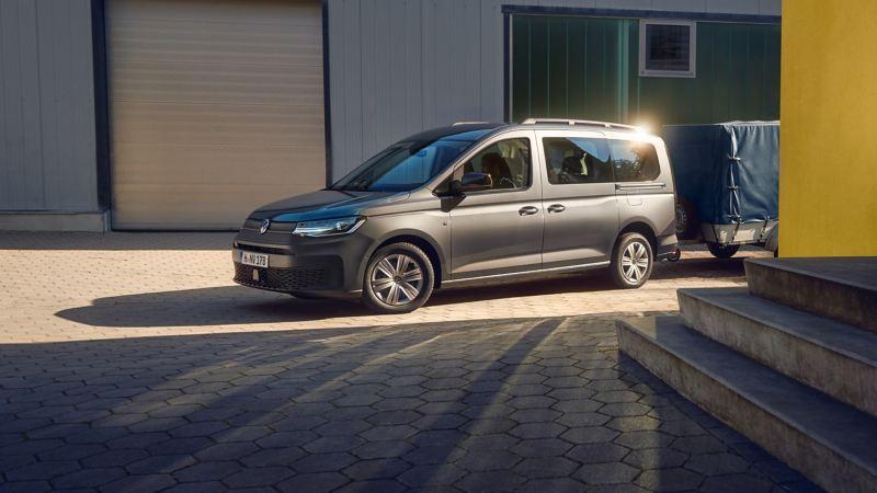Ein Volkswagen Nutzfahrzeuge Caddy Kombi mit Anhänger steht vor einem Häuserkomplex.