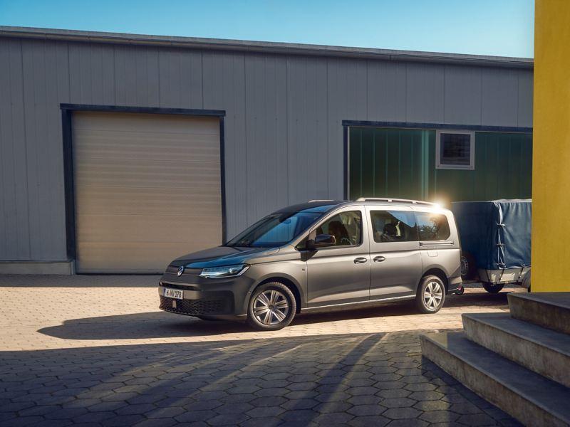 Ein Volkswagen Caddy Kombi mit Anhänger steht vor einem Häuserkomplex.