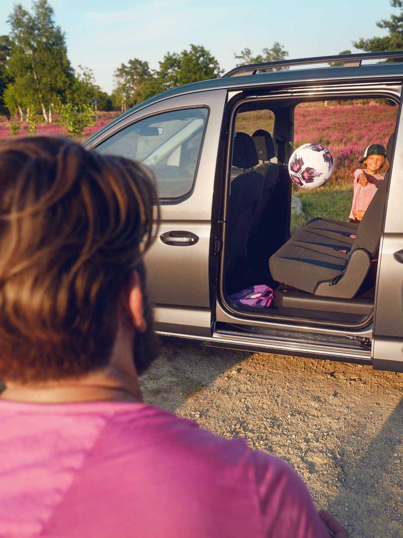 Chłopiec rzucający piłkę przez otwarte drzwi Nowego Caddy