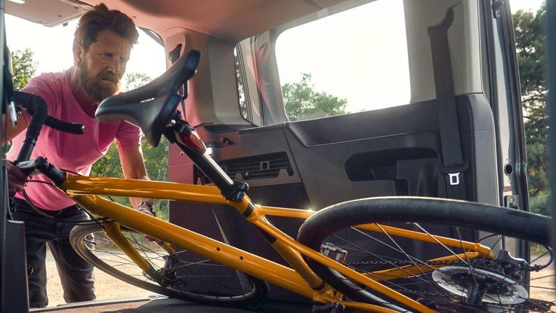 Ein Mann lädt ein Fahrrad in den neuen Caddy Kombi.