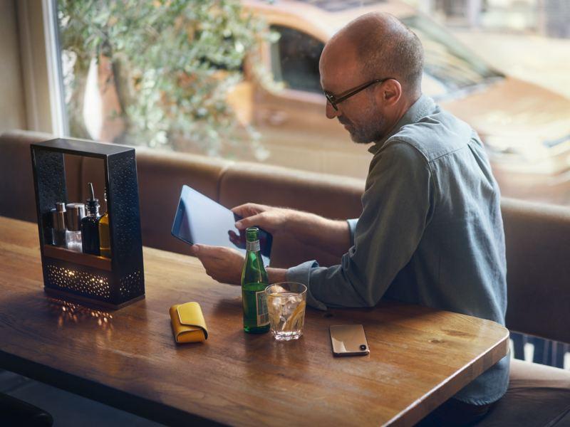 Um homem com um tablet na mão sentado à mesa. Em segundo plano, a nova Caddy.