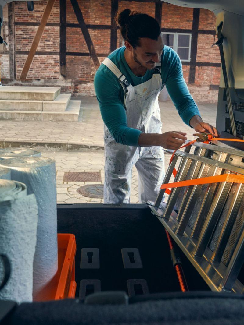 Ein Mann verzurrt eine Leiter in den neuen Caddy Kombi.