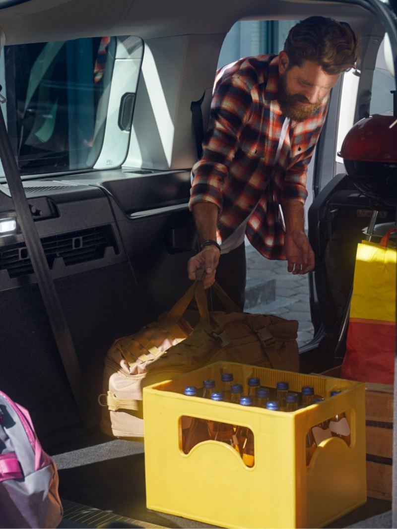 Zwei Männer beladen den neuen Caddy Kombi mit Reisegepäck und Getränkekästen.