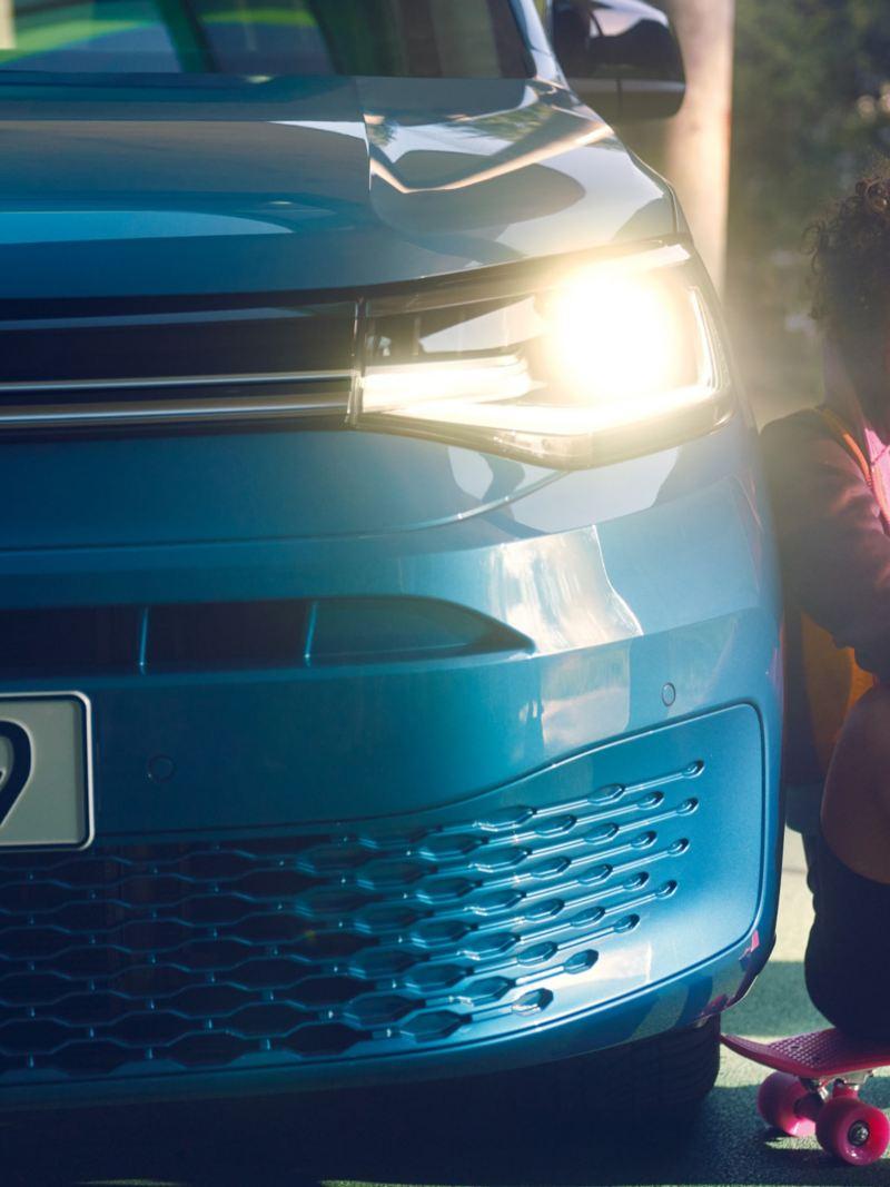 Eine Frau neben den leuchtenden Scheinwerfern des neuen Caddy.