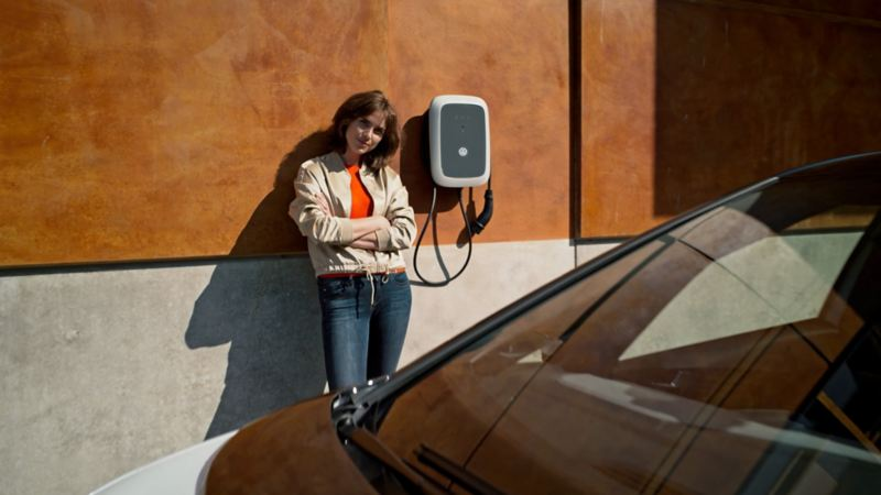 Woman stook next to ID. Charger Pro wallbox