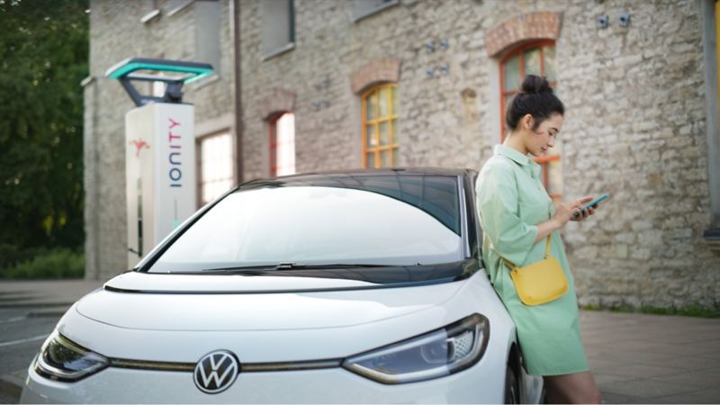 Women looking at her phone leaning against electric car