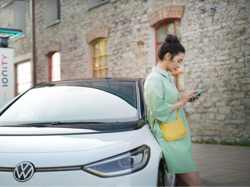 A woman leans against the VW ID.3 while the vehicle is charging at an IONITY charging station.