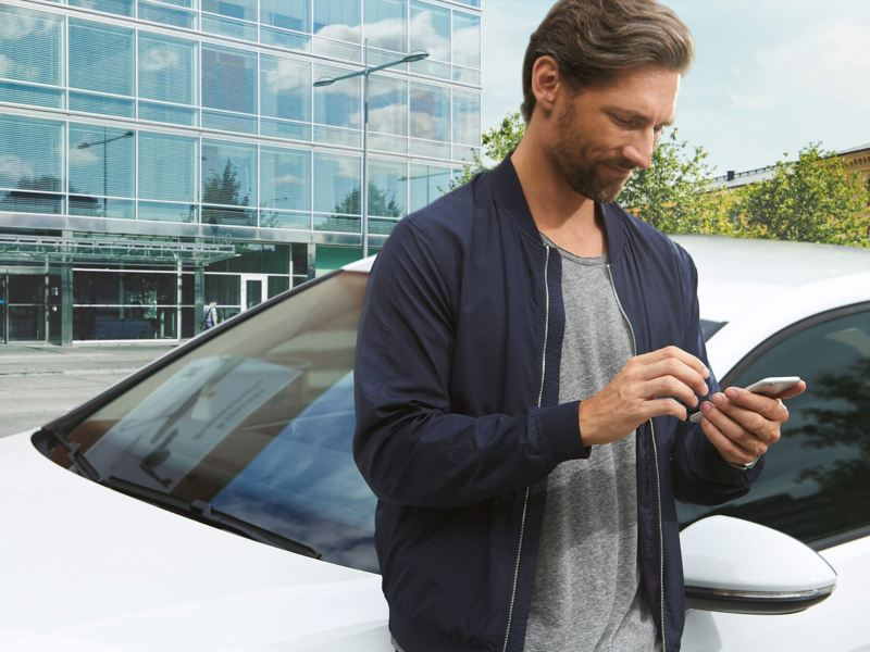 A man using his smart phone, next to a sliver Volkswagen Golf.