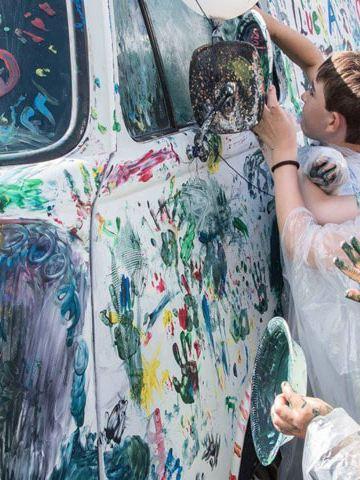 No Festival de Verão Pão de Forma 2017, as crianças pintam com os dedos e tintas coloridas uma carrinha Pão de Forma branca.