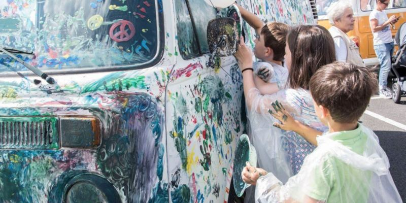 Beim Bulli Summer Festival 2017 bemalen Kinder einen weißen Bulli mit bunter Fingerfarbe.