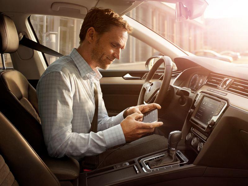 Hombre sentado en el puesto de conducción de un Volkswagen comercial usando un móvil con MirrorLink